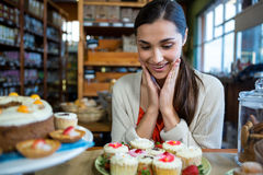 Happy woman looking at cupcakes Royalty Free Stock Photos