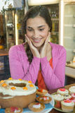 Happy woman looking at dessert display Royalty Free Stock Photos