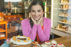 Happy woman looking at dessert display Stock Image