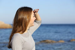 Happy woman looking forward at the horizon. Happy woman on the beach looking forward at the horizon with her hand in forehead Royalty Free Stock Photos