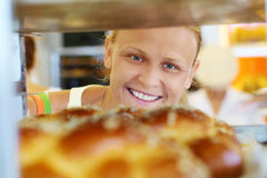 Happy woman looking at fresh bread in the shop Stock Photography