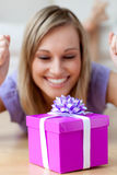 Happy woman looking at a gift lying on the floor Stock Image