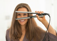 Happy woman looking through hair straightener Royalty Free Stock Image