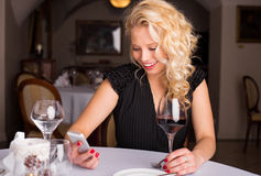 Happy woman looking at her phone while having wine Royalty Free Stock Image