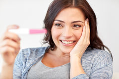 Happy woman looking at home pregnancy test Royalty Free Stock Image