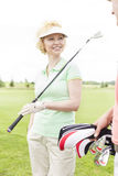 Happy woman looking at male friend at golf course Royalty Free Stock Photos