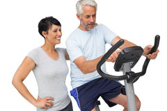 Happy woman looking at mature man on stationary bike Royalty Free Stock Photography