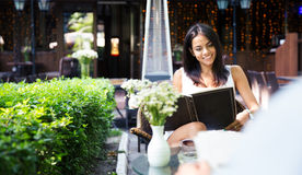 Happy woman looking at menu in cafe. Happy young woman looking at menu in outdoors cafe Royalty Free Stock Photography
