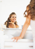 Happy woman looking in mirror in bathroom. Happy woman with long hair looking in mirror in bathroom stock photography