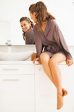 Happy woman looking in mirror in bathroom. Happy young woman looking in mirror in modern bathroom stock photography
