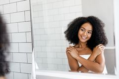 Happy woman looking at mirror. With hands on her chest Stock Images
