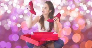 Happy woman looking at new red shoes over bokeh Stock Images