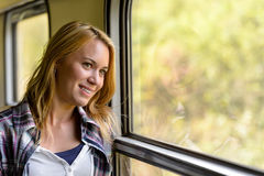 Happy woman looking out train window pensive Stock Photo