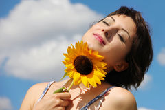 Happy woman looking peaceful. Beautiful woman smiling and looking peaceful while holding a sunflower Royalty Free Stock Photography