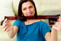 Happy woman looking on a photo film at home. Focus on a photo film. Stock Images