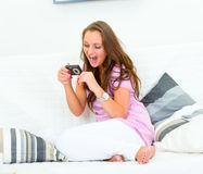Happy woman looking photos in camera on sofa Royalty Free Stock Images