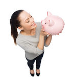 Happy woman looking at piggy bank Stock Image