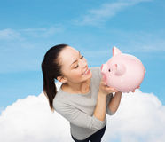 Happy woman looking at piggy bank Stock Photo