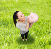 Happy woman looking at piggy bank Royalty Free Stock Photos