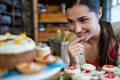 Happy woman looking at a plate of cupcakes Stock Photography