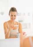 Happy woman looking on pregnancy test in bathroom Stock Image