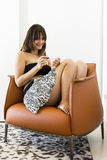 Happy woman looking a pregnancy test. While sitting in an armchair Stock Photos