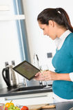 Happy woman looking recipe tablet kitchen reading. Cooking Royalty Free Stock Photos