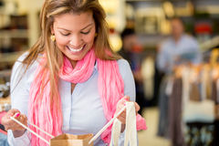 Woman looking into a shopping bag Stock Images