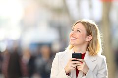 Happy woman looking at side holding phone in the street royalty free stock photo
