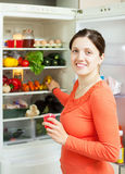 Happy woman looking for something in fridge Stock Image