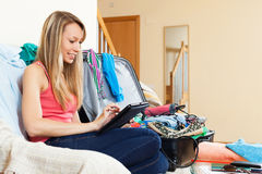 Happy woman looking tablet  with travel baggage Stock Photo