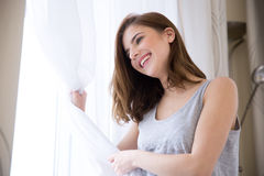 Happy woman looking at window Royalty Free Stock Photography