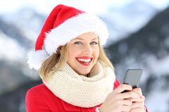 Happy woman looking at you holding phone in christmas. With a snowy mountain in the background Royalty Free Stock Photo