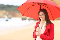 Happy woman looks at camera holding a red umbrella royalty free stock photo