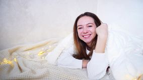 Happy woman looks at camera and smiles, lying on floor covered by blanket in bright room next to garland. stock footage