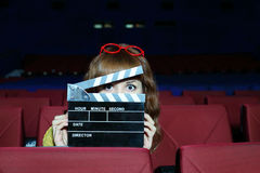 Happy woman looks through clap board. Happy beautiful woman looks through clap board in auditorium of movie theater Royalty Free Stock Photo