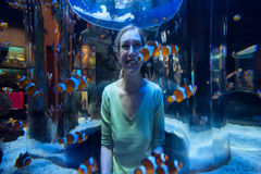 Happy woman looks at clown fish through glass Royalty Free Stock Images