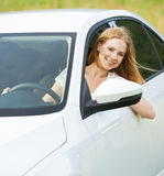 Happy woman looks out the car window on nature Royalty Free Stock Images