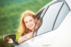 Happy woman looks out the car window on nature Stock Images