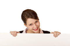 Happy woman looks smiling above blank ad board Royalty Free Stock Photo