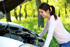 Happy woman looks under hood car. Background green park Royalty Free Stock Images