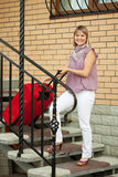 Happy woman with luggage. On her home  stages Royalty Free Stock Images