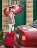 Happy woman with  luggage. Near fence wicket  in front of home Royalty Free Stock Image