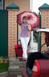 Happy woman with luggage. Go to car from home Royalty Free Stock Photography