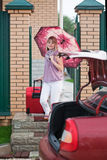 Happy woman with luggage. Go to car from home Stock Photo