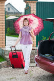 Happy woman with luggage. Go to car from home Stock Photography