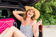 Happy woman with luggage in car trunk. Travel concept. Woman with luggage in car trunk. Travel concept Stock Photos