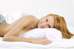 Happy woman lying in bed Royalty Free Stock Photography