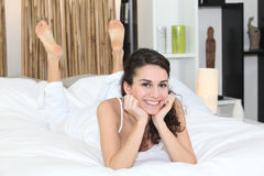 Happy woman lying in bed Stock Photo
