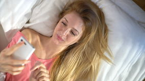 Happy woman lying on bed in the morning, using the smartphone and smiling stock footage